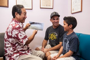 Dr. Dean Sueda consulting with father and son
